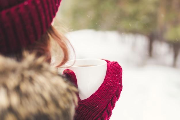 Mädchen, das eine kaffeetasse in den roten handschuhen im wald hält
