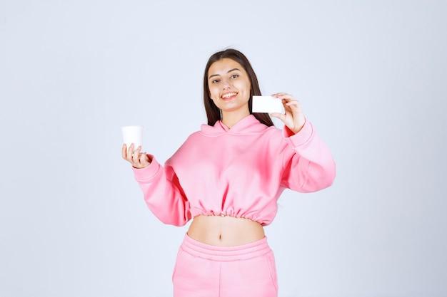 Mädchen, das eine kaffeetasse in einer hand hält und ihre visitenkarte in einer anderen hand präsentiert
