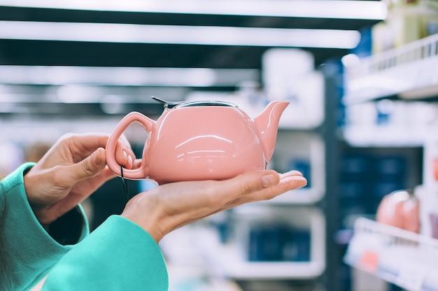 Mädchen, das eine keramische rosa teekanne in einem supermarkt hält.
