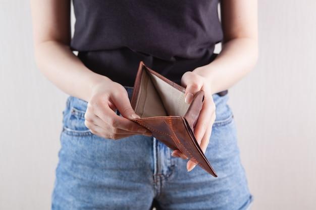 Mädchen, das eine leere brieftasche in ihrer hand hält