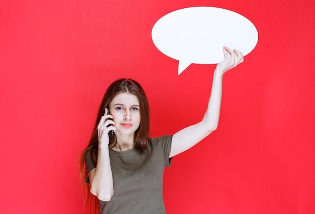 Mädchen, das eine leere ovale infotafel hält und mit dem telefon spricht.