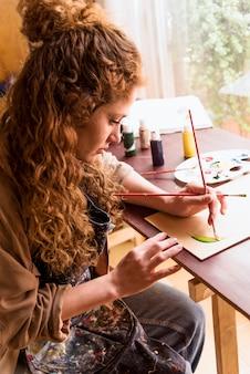 Mädchen, das eine leinwand im kunststudio malt