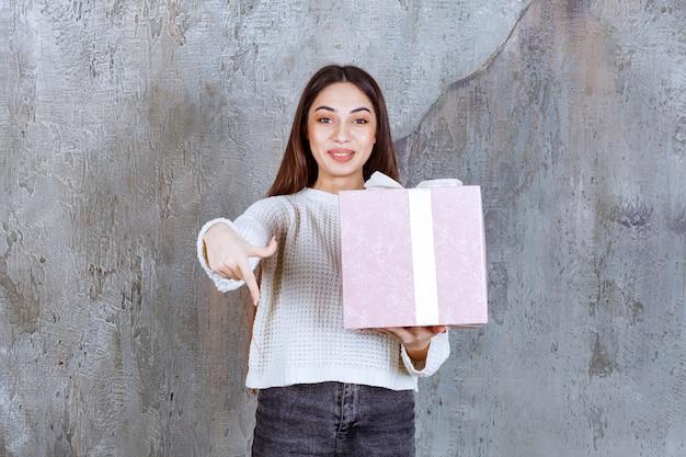 Mädchen, das eine lila geschenkbox hält, die mit weißem band umwickelt ist und jemanden einlädt, es zu präsentieren.