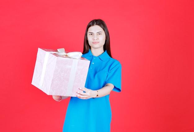 Mädchen, das eine lila geschenkbox hält, die mit weißem band umwickelt ist, und sieht verwirrt und nachdenklich aus