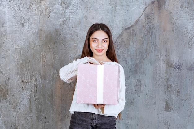 Mädchen, das eine lila geschenkbox hält, die mit weißem band umwickelt ist.