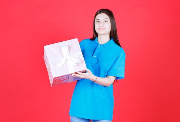 Mädchen, das eine lila geschenkbox hält, die mit weißem band umwickelt ist