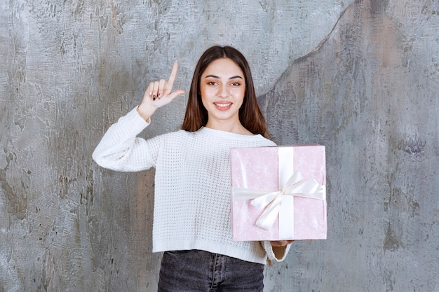 Mädchen, das eine lila geschenkbox mit weißem band hält und nachdenklich aussieht oder eine gute idee hat.