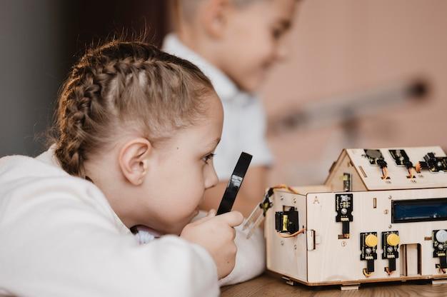 Mädchen, das eine lupe verwendet, um elektrische komponenten zu betrachten