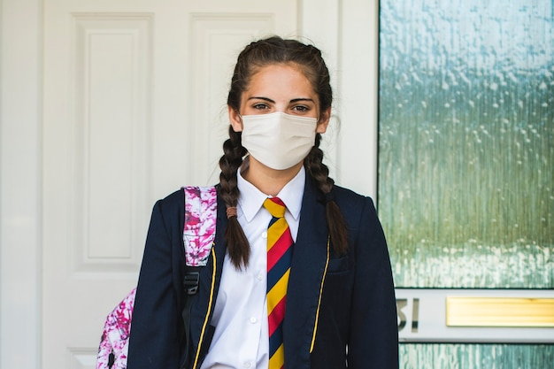 Mädchen, das eine maske trägt und in der neuen normalität zur schule geht