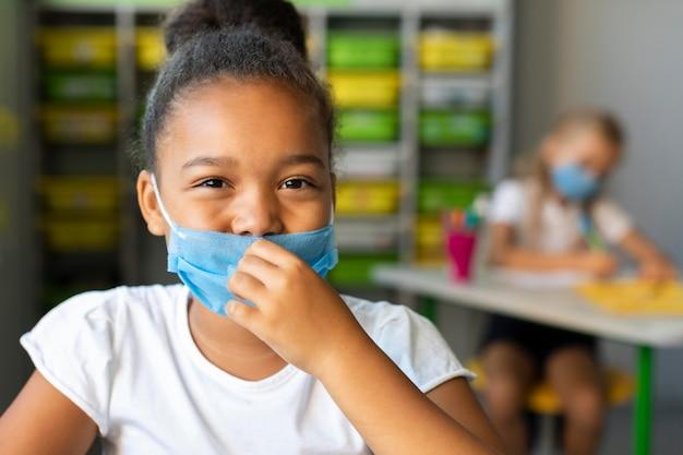 Mädchen, das eine medizinische maske aufsetzt