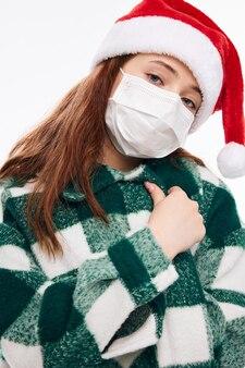 Mädchen, das eine medizinische maske neujahrsrothut-plaidmantel-nahaufnahme trägt. hochwertiges foto