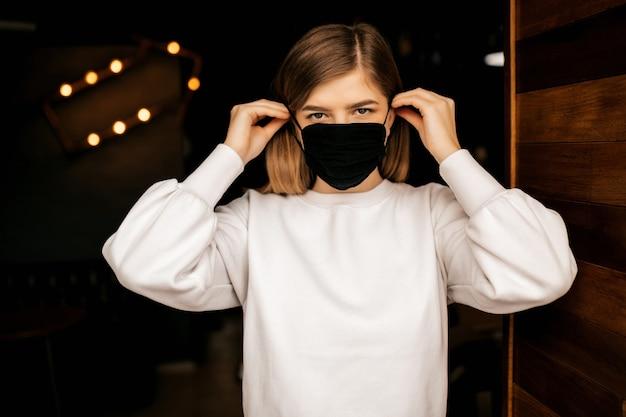 Mädchen, das eine medizinische schwarze maske aufsetzt