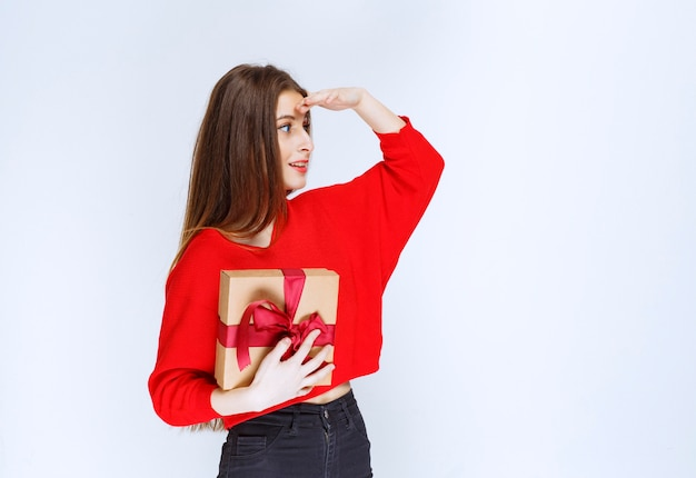 Mädchen, das eine mit rotem band umwickelte pappgeschenkbox hält und auf jemanden zeigt.