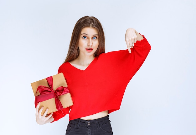 Mädchen, das eine mit rotem band umwickelte pappgeschenkbox hält und jemanden einlädt, es zu erhalten.