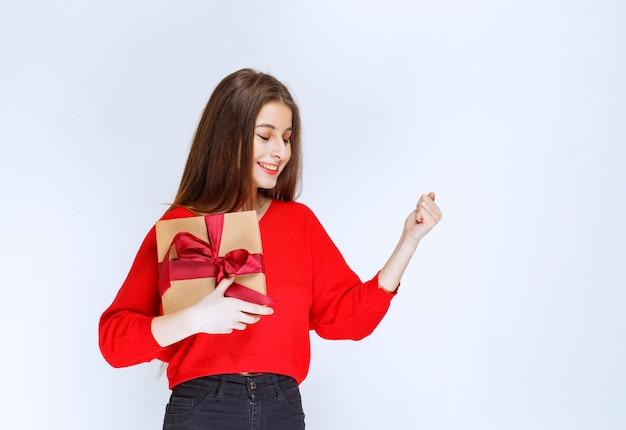 Mädchen, das eine mit rotem band umwickelte pappgeschenkbox hält und zufriedenheitszeichen zeigt.