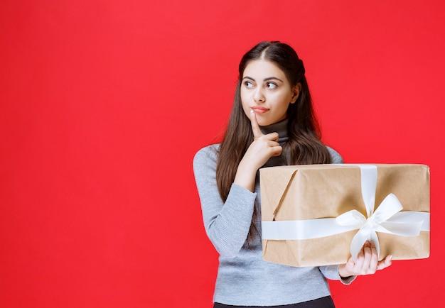Mädchen, das eine pappgeschenkbox hält und denkt.