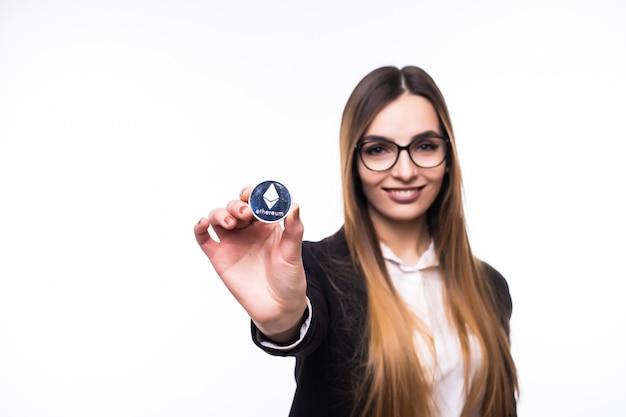 Mädchen, das eine physische kryptowährung der ethereum-münze in ihrer hand hält