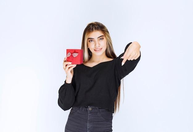 Mädchen, das eine rote geschenkbox hält und bemerkt, dass jemand kommt und sie empfängt. foto in hoher qualität