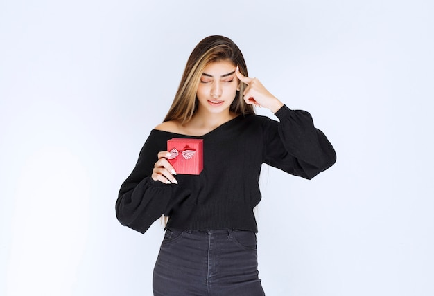 Mädchen, das eine rote geschenkbox hält und denkt oder zögert. foto in hoher qualität