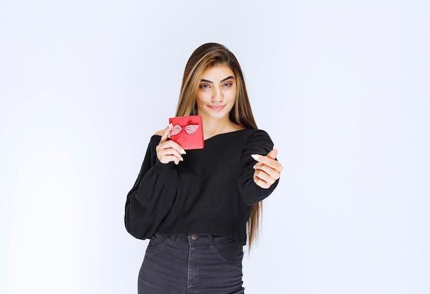 Mädchen, das eine rote geschenkbox hält und jemanden anruft, um es zu präsentieren. foto in hoher qualität
