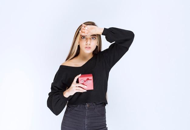 Mädchen, das eine rote geschenkbox hält und sieht verängstigt und gestresst aus. foto in hoher qualität