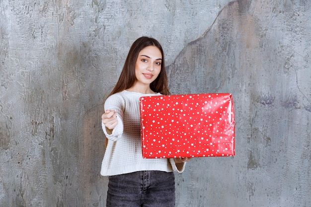 Mädchen, das eine rote geschenkbox mit weißen punkten darauf hält und um zahlung bittet.