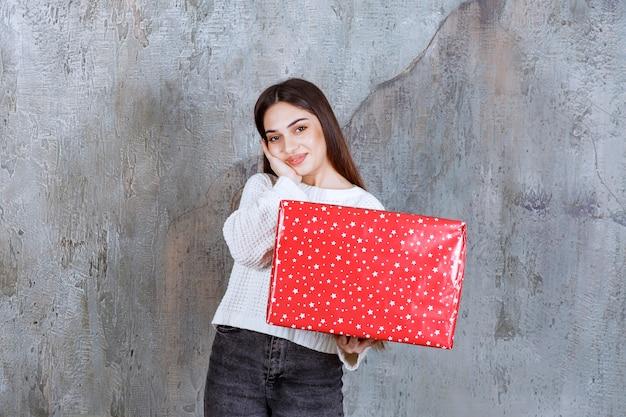 Mädchen, das eine rote geschenkbox mit weißen punkten darauf hält