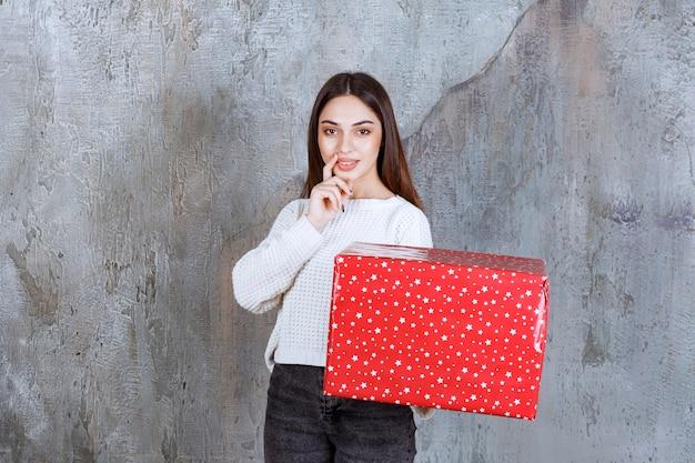 Mädchen, das eine rote geschenkbox mit weißen punkten hält und nachdenklich und verträumt aussieht.