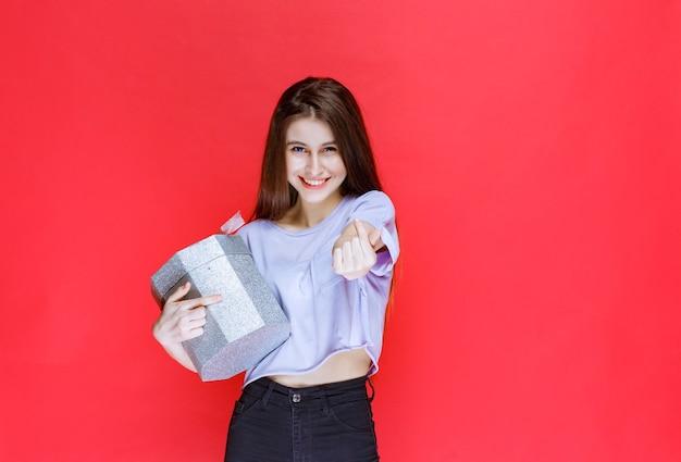Mädchen, das eine silberne geschenkbox hält und die person bittet, in die nähe zu kommen, um sie zu erhalten.