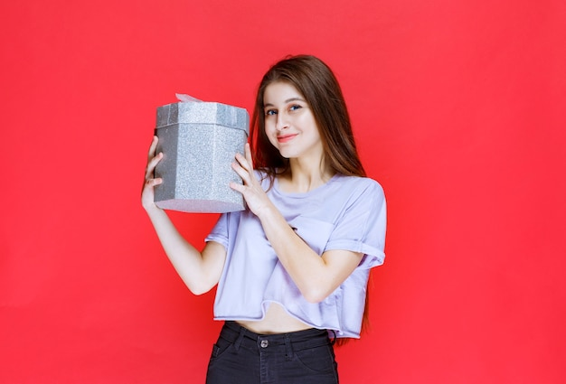 Mädchen, das eine silberne geschenkbox hält und fördert.