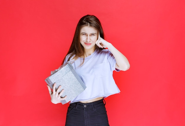 Mädchen, das eine silberne geschenkbox hält und nachdenklich aussieht.