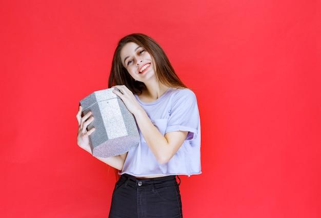 Mädchen, das eine silberne geschenkbox hält und sich glücklich fühlt.