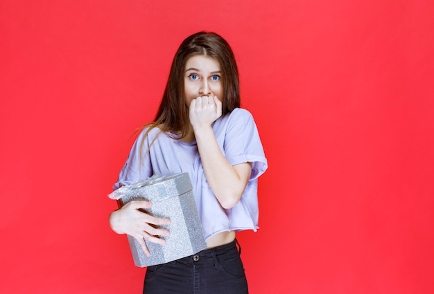 Mädchen, das eine silberne geschenkbox hält und sieht deprimiert und verwirrt aus.