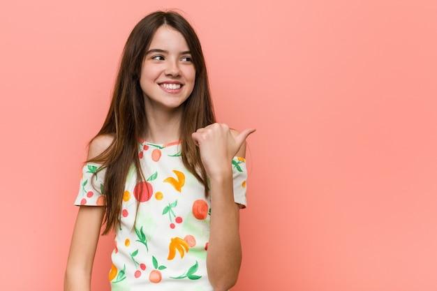 Mädchen, das eine sommerkleidung gegen eine rote wand zeigt, zeigt mit daumenfinger weg, lachend und sorglos.