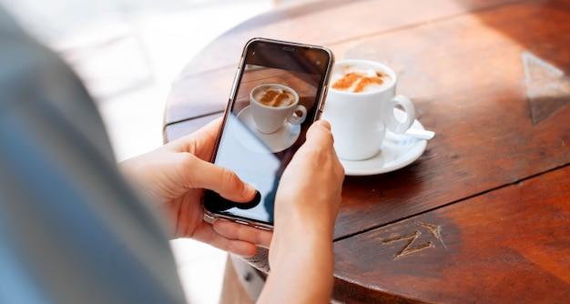 Mädchen, das eine tasse kaffee fotografiert