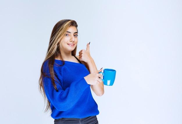 Mädchen, das eine tasse kaffee trinkt und den geschmack genießt.