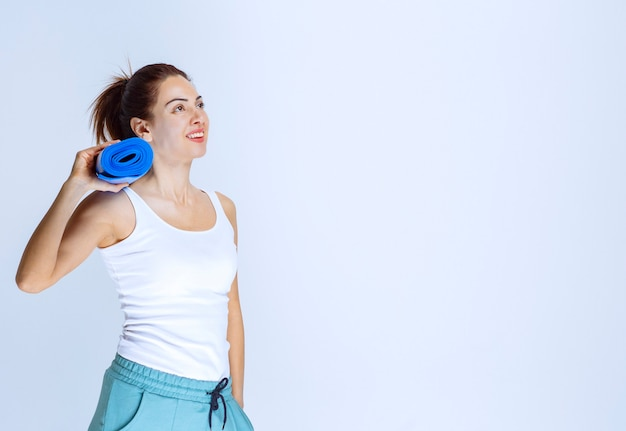 Mädchen, das eine unschärfe hält, rollte yogamatte auf.