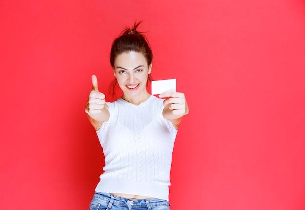 Mädchen, das eine visitenkarte hält und ihre neue position genießt.