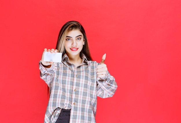 Mädchen, das eine visitenkarte hält und zufriedenheitszeichen zeigt