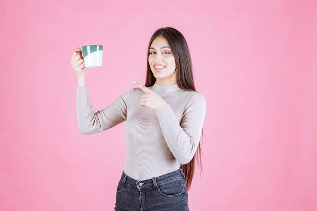 Mädchen, das eine weiße grüne farbe kaffeetasse hält und sich positiv fühlt