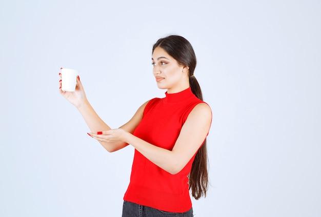 Mädchen, das eine weiße kaffeetasse hält und darauf zeigt.