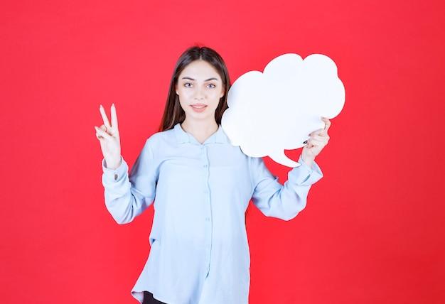 Mädchen, das eine wolkenform-infotafel hält und positives handzeichen zeigt.