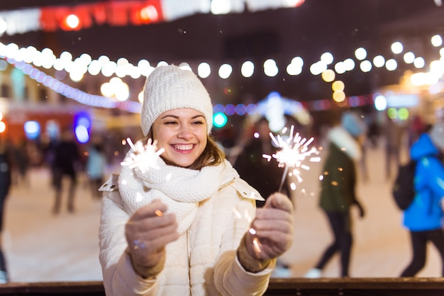 Mädchen, das eine wunderkerze in der hand hält. winterstadthintergrund im freien, schnee, schneeflocken.