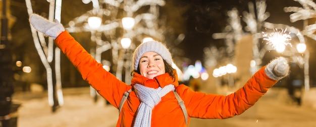 Mädchen, das eine wunderkerze in der hand hält winterstadthintergrund-schneeflocken im freien