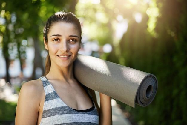Mädchen, das eine yogamatte bereit hält, um ihren gesunden tag zu beginnen