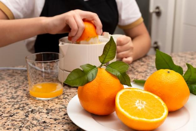 Mädchen, das eine zitruspresse mit orange und frischen zitrusfrüchten in der küche hält