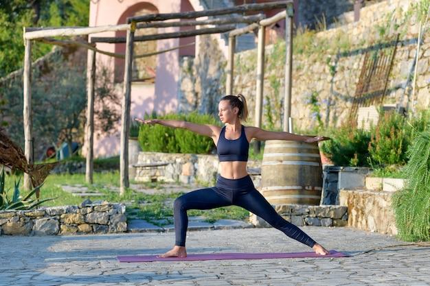Mädchen, das eine zweite krieger-yoga-pose durchführt, während im sonnenschein des frühen morgens draußen trainiert
