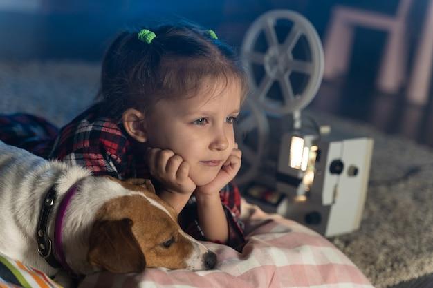 Mädchen, das einen alten film auf einem retro-weinlesefilmprojektor mit einem hund sieht