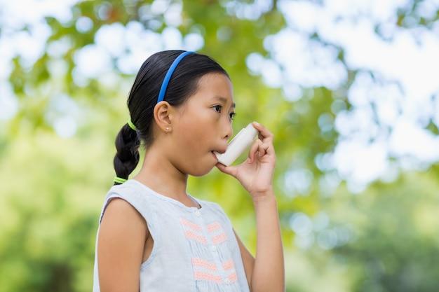 Mädchen, das einen asthmainhalator verwendet