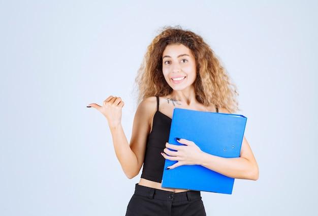 Mädchen, das einen blauen aufgabenordner hält und auf ihren freund zeigt.